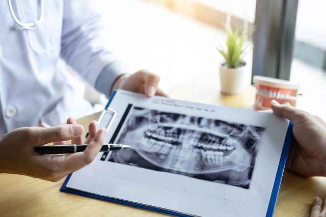 歯のレントゲン写真を見せる歯科医